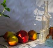 Pommes jaunes rouges brouill?es, grenade rouge, feuille en bon ?tat et bouteilles de cru au soleil avec des ombres Fin vers le ha photographie stock