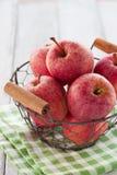 Pommes juteuses rouges fraîches dans un panier sur un textile vert sur un fond en bois Image stock