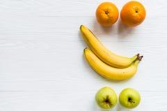 Pommes, oranges et bananes fraîches sur le blanc Images stock
