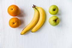 Pommes, oranges et bananes fraîches sur le blanc Photos stock