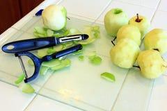 Pommes organiques étant épluchées pour la cuisson Image libre de droits