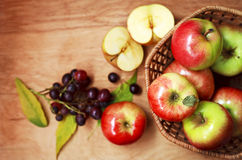 Pommes organiques dans un panier sur une table en bois Photographie stock