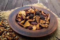 Pommes, poires, abricots, baies et écrous de fruits secs dans une cuvette sur le fond en bois foncé Photo libre de droits
