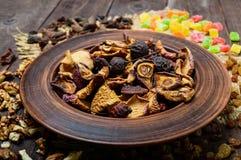 Pommes, poires, abricots, baies, raisins secs et écrous de fruits secs dans une cuvette sur le fond en bois foncé Photo libre de droits