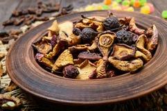 Pommes, poires, abricots, baies, raisins secs et écrous de fruits secs dans une cuvette sur le fond en bois foncé Photo stock