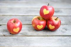 Pommes rouges avec la forme du coeur sur un fond en bois gris Photographie stock