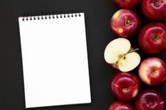 Pommes rouges crues fraîches et carnet vide sur le fond noir, vue supérieure Configuration plate, aérienne, d'en haut L'espace po photos stock