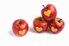 Pommes rouges d'isolement avec la forme du coeur sur un fond blanc Image stock