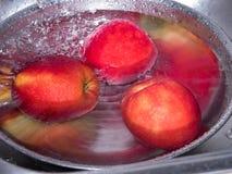 Pommes rouges dans l'eau, dans la cuvette d'acier inoxydable avec une baisse de wate Photo stock