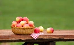 Pommes rouges et jaunes dans le panier sur le Tableau en bois rugueux Photographie stock libre de droits