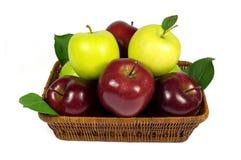 Pommes rouges et vertes fraîches avec des feuilles dans le panier en osier d'isolement sur le blanc Photographie stock libre de droits