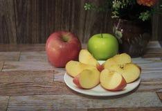 Pommes rouges et vertes sur le plancher en bois Images stock