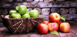 Pommes rouges mûres et pomme verte sur le fond en bois Image libre de droits