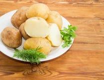 Pommes vapeur en leurs peaux et herbes sur le plan rapproché de plat Image libre de droits