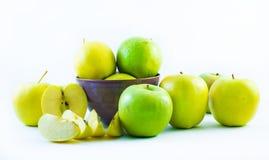 Pommes vertes et jaunes dans une tasse et des tranches de pommes sur un fond blanc Image stock