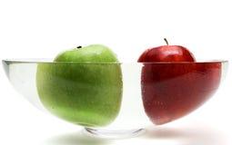 Pommes vertes et rouges dans le vase avec de l'eau Images stock