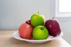 Pommes vertes et rouges mûres sur le fond blanc de table Image libre de droits