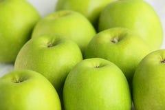 Pommes vertes fraîches sur un plat blanc Photographie stock