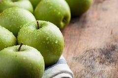Pommes vertes mûres dans une cuvette en bois sur une vieille table rustique Fruits utiles sur le fond en bois Avec l'espace de co Photographie stock