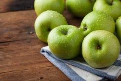 Pommes vertes mûres dans une cuvette en bois sur une vieille table rustique Fruits utiles sur le fond en bois Avec l'espace de co Image stock