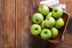 Pommes vertes mûres dans une cuvette en bois sur une vieille table rustique Fruits utiles sur le fond en bois Vue supérieure avec Photo libre de droits