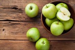 Pommes vertes mûres dans une cuvette en bois sur une vieille table rustique Fruits utiles sur le fond en bois Vue supérieure avec Photos stock