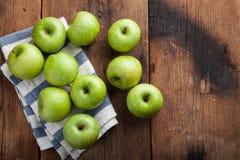 Pommes vertes mûres dans une cuvette en bois sur une vieille table rustique Fruits utiles sur le fond en bois Vue supérieure avec Photographie stock libre de droits