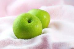 Pommes vertes sur le tissu rose image stock