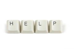 Pomoc od rozrzuconych klawiaturowych kluczy na bielu Zdjęcie Stock