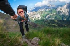 Pomocna dłoń pomaga dziewczyny w górach bierze ona h Zdjęcia Stock