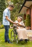 Pomocnicza daje fili?anka herbata szcz??liwa starsza kobieta w w?zku inwalidzkim w ogr?dzie fotografia stock
