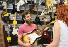 Pomocnicza pokazuje klient gitara przy muzycznym sklepem obraz stock
