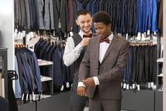 Pomocniczy wybiera kostium w modnym butiku dla klienta zdjęcia stock