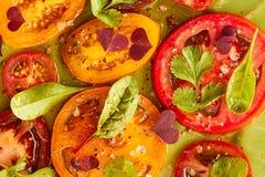 Pomodori affettati con le spezie e l'olio su verde Fotografia Stock