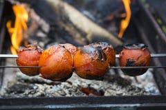 Pomodori arrostiti sullo spiedo con succo e fuoco Fotografia Stock