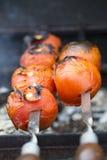 Pomodori arrostiti sullo spiedo con succo e fuoco Immagine Stock