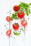 Pomodori, basilico ed aglio sulla tavola di legno bianca Immagini Stock