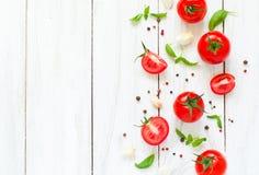 Pomodori, basilico ed aglio sulla tavola di legno bianca Fotografia Stock