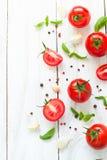 Pomodori, basilico ed aglio sulla tavola di legno bianca Immagine Stock