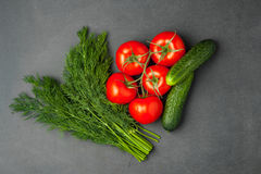 Pomodori, cetrioli ed aneto verde su un fondo scuro Concetto dell'alimento Vista superiore Fotografia Stock Libera da Diritti