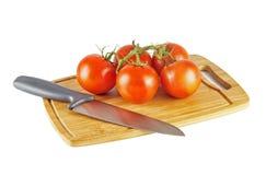 Pomodori che si trovano sul tagliere e sul coltello Immagine Stock