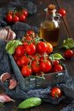Pomodori ciliegia, aglio, basilico e olio d'oliva fotografia stock libera da diritti