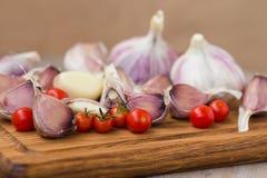 Pomodori ciliegia, aglio e sale marino freschi su vecchio Fotografie Stock