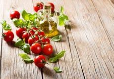 Pomodori ciliegia con basilico e olio d'oliva fotografia stock libera da diritti