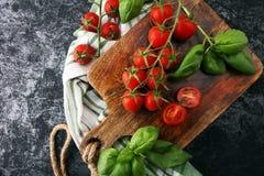 Pomodori ciliegia con il towl del piatto e del basilico sul tagliere Fotografia Stock Libera da Diritti