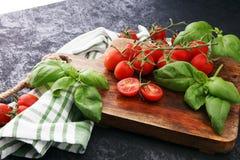 Pomodori ciliegia con il towl del piatto e del basilico sul tagliere Immagini Stock
