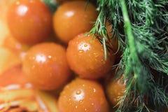 Pomodori ciliegia con prezzemolo ed aneto sul piatto arancio Immagini Stock
