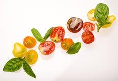 Pomodori ciliegia e foglie affettati del basilico su fondo bianco Fotografia Stock
