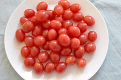 Pomodori ciliegia e piatto della porcellana di osso fotografia stock libera da diritti