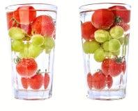 Pomodori ciliegia ed uva in glas con isolata acqua, due versioni di un cocktail Fotografia Stock